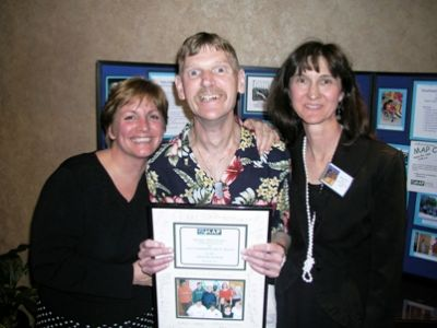 Photo - M.A. Wiland and Jackie Macy help a proud David Frantom show off Altarum's Community Spirit award.