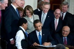 Photo of President Obama signing the PPACA