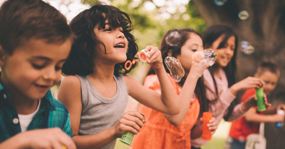 A diverse group of children blowing bubbles on a summer day.