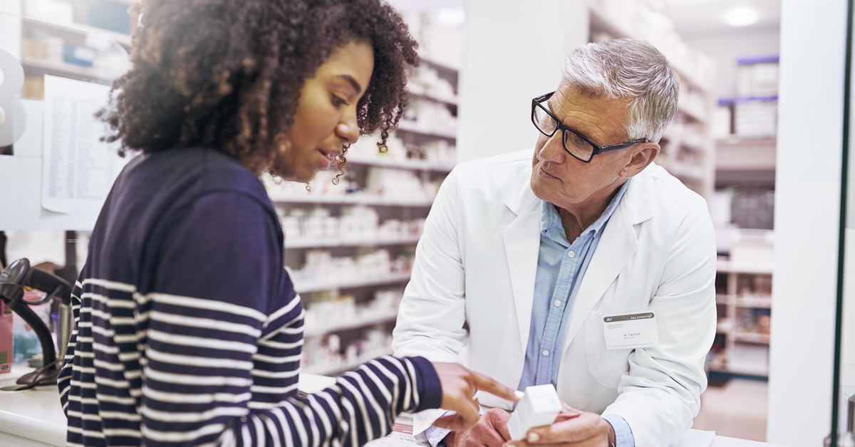 Stock photo of woman asking a male pharmacist questions at checkout.