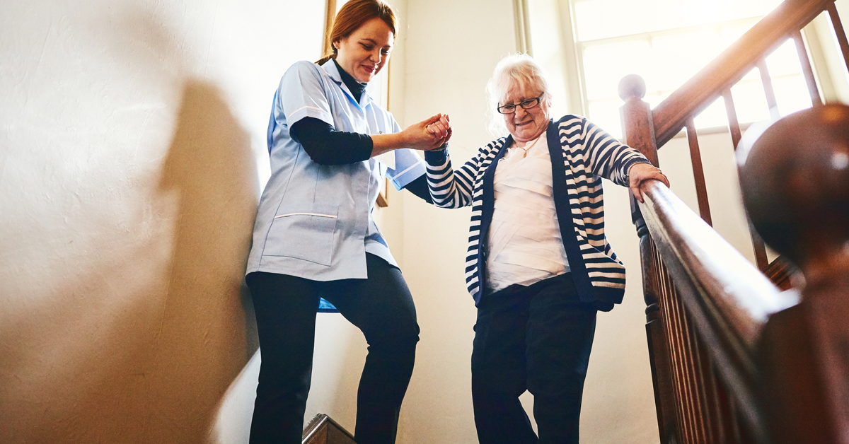 Stock photo of a careworker helping an elderly woman descend a stairway.