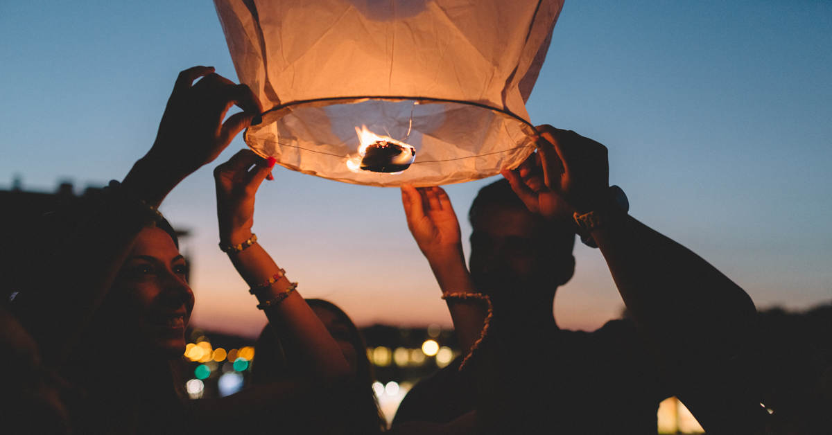 Stock photo of young people lighting paper lanterns on a rooftop.